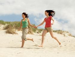 To kvinder løber en tur på stranden om sommeren